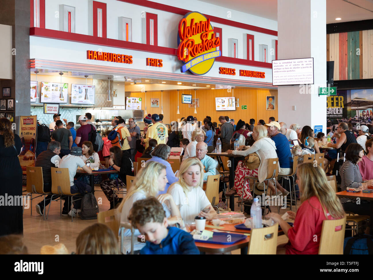 People eating and drinking at the Johnny Rockets restaurant, departures, Terminal 3, Cancun airport Mexico - Stock Image