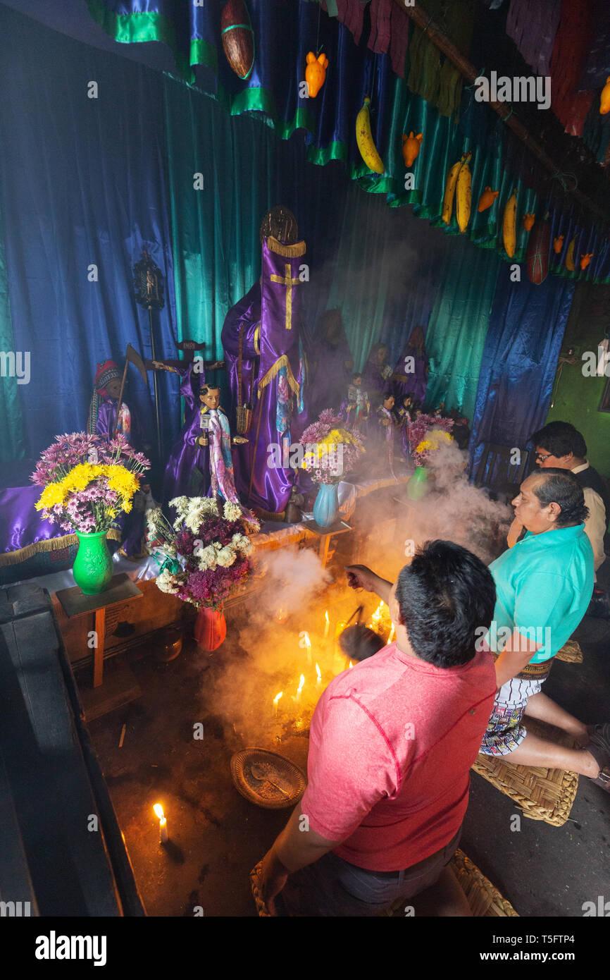 Local mayan people worshipping the image of Maximon, or San Simon, a traditional Mayan deity or folk saint, Santiago Atitlan Guatemala Central America Stock Photo
