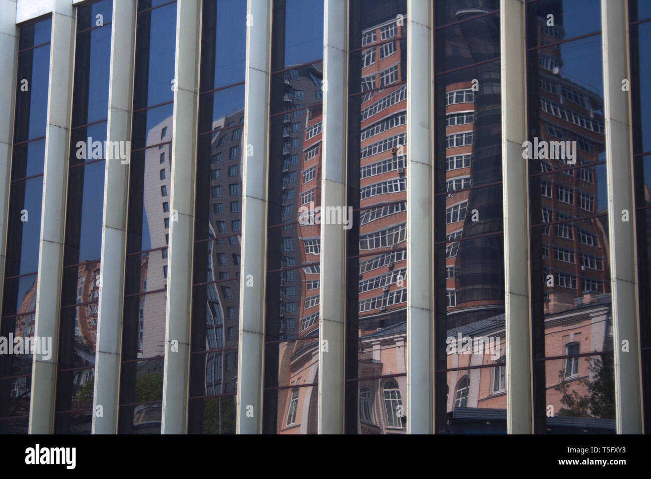 Cityscape reflection on building striped glass wall with distortion effect in downtown district on a spring day - Stock Image