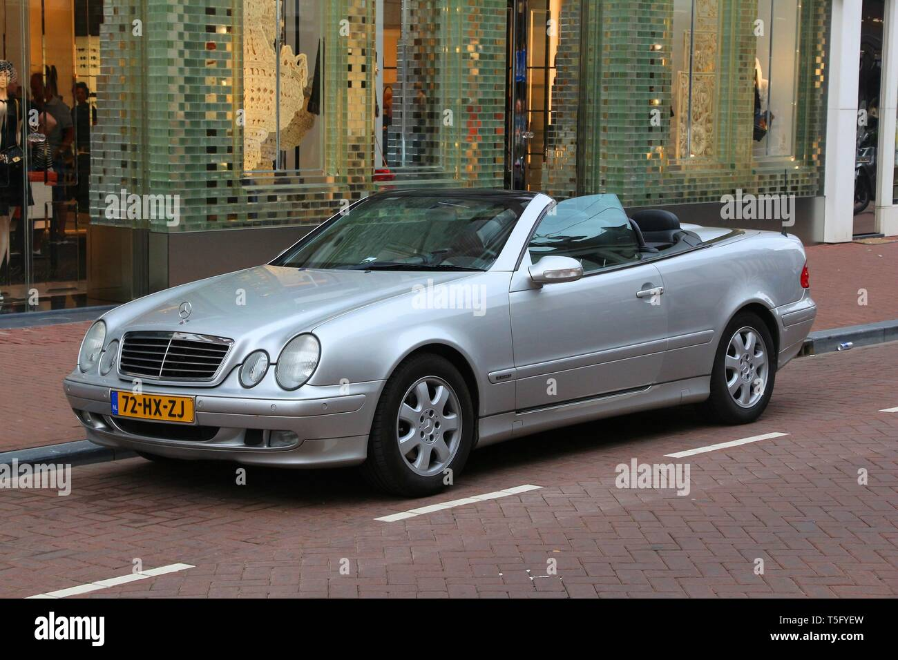 AMSTERDAM, NETHERLANDS - JULY 10, 2017: Silver Mercedes-Benz E-class convertible car parked in Amsterdam. Netherlands has 528 registered cars per 1,00 Stock Photo