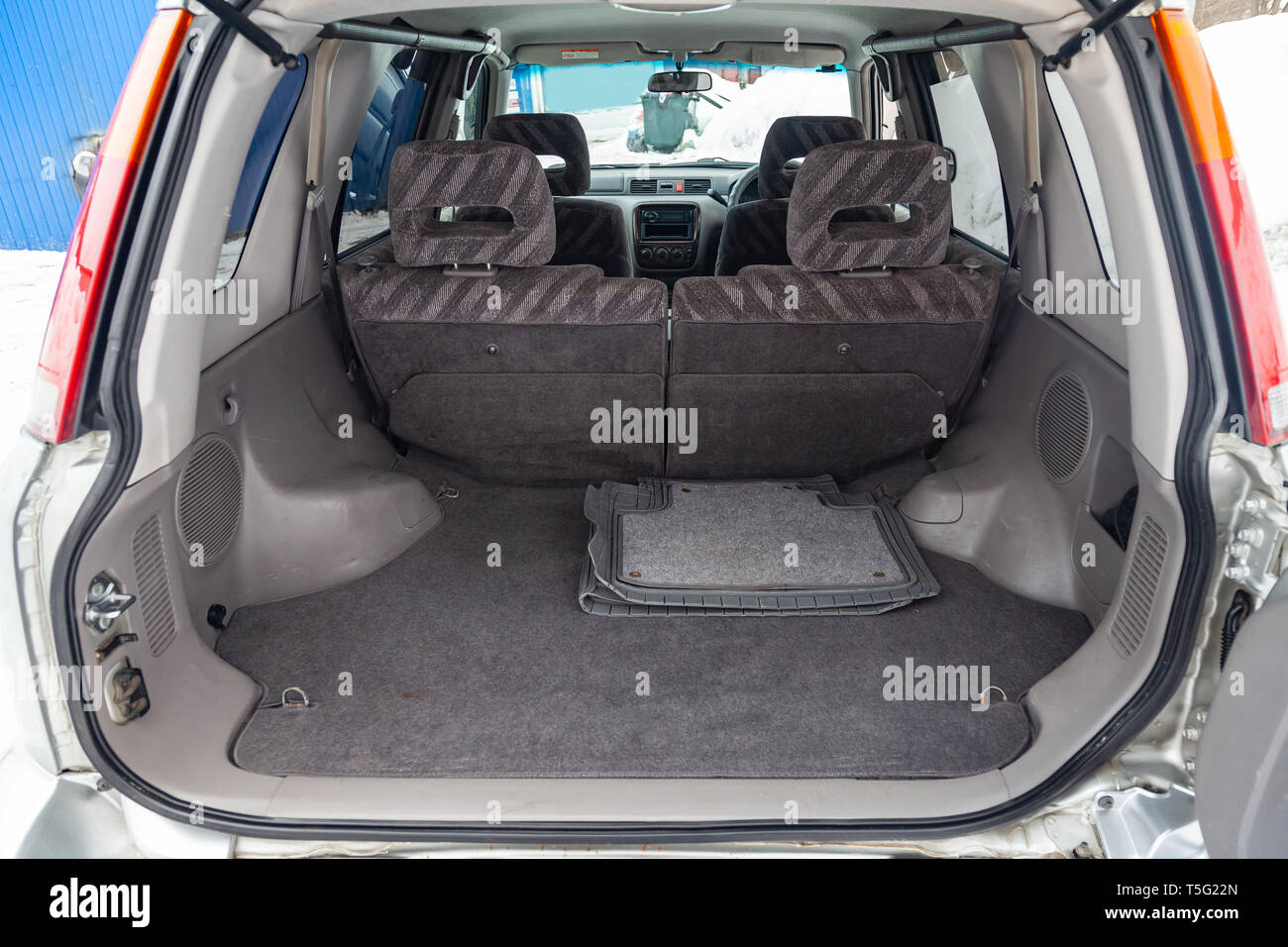 View to the gray color interior of suv car with trunk luggage compartment with striped fabric upholstery after cleaning and detailing in the vehicle r - Stock Image