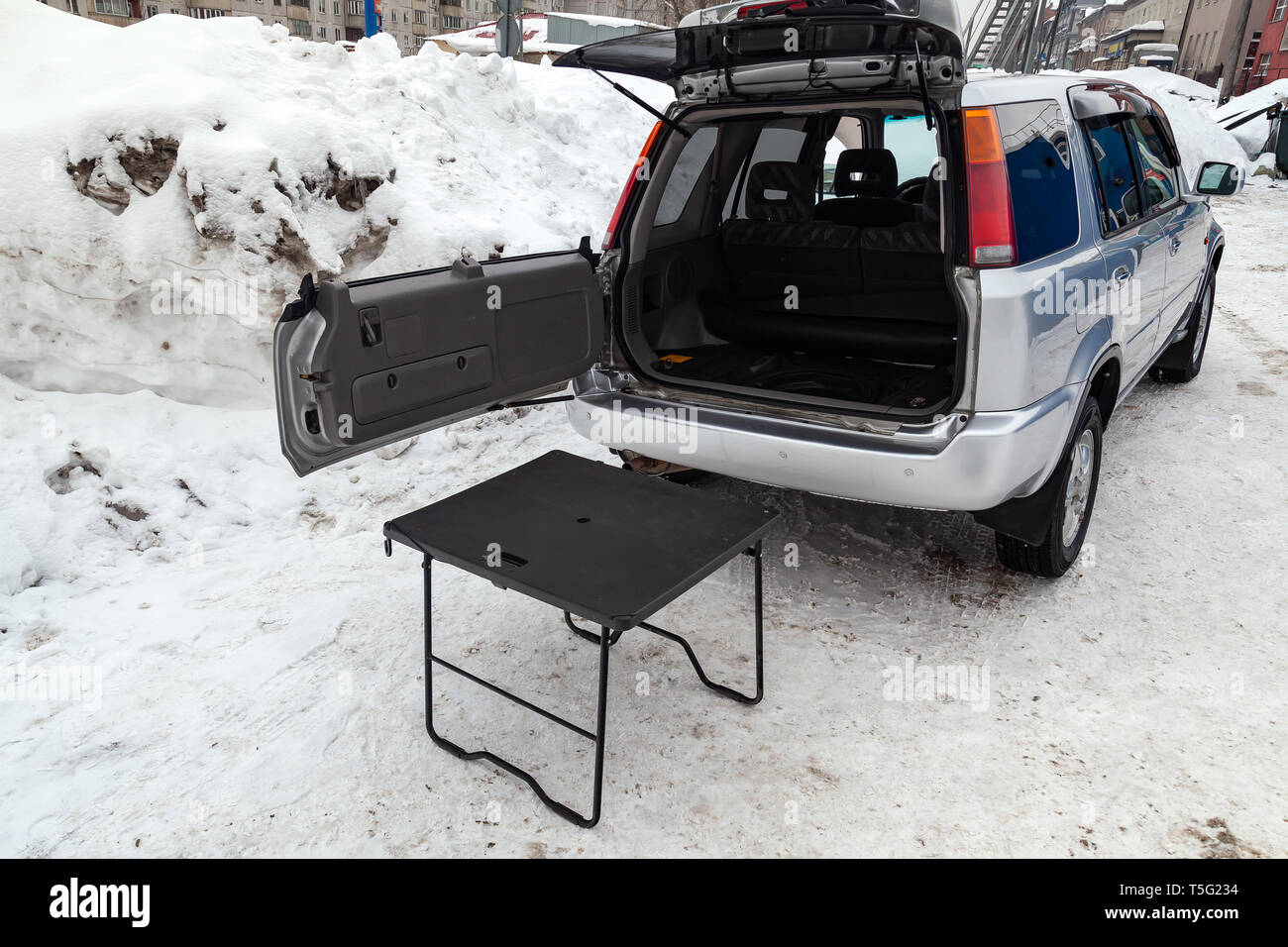 SUV car in silver color with opened trunk and table for picnic near it after cleaning before sale in a winter day and snow background - Stock Image