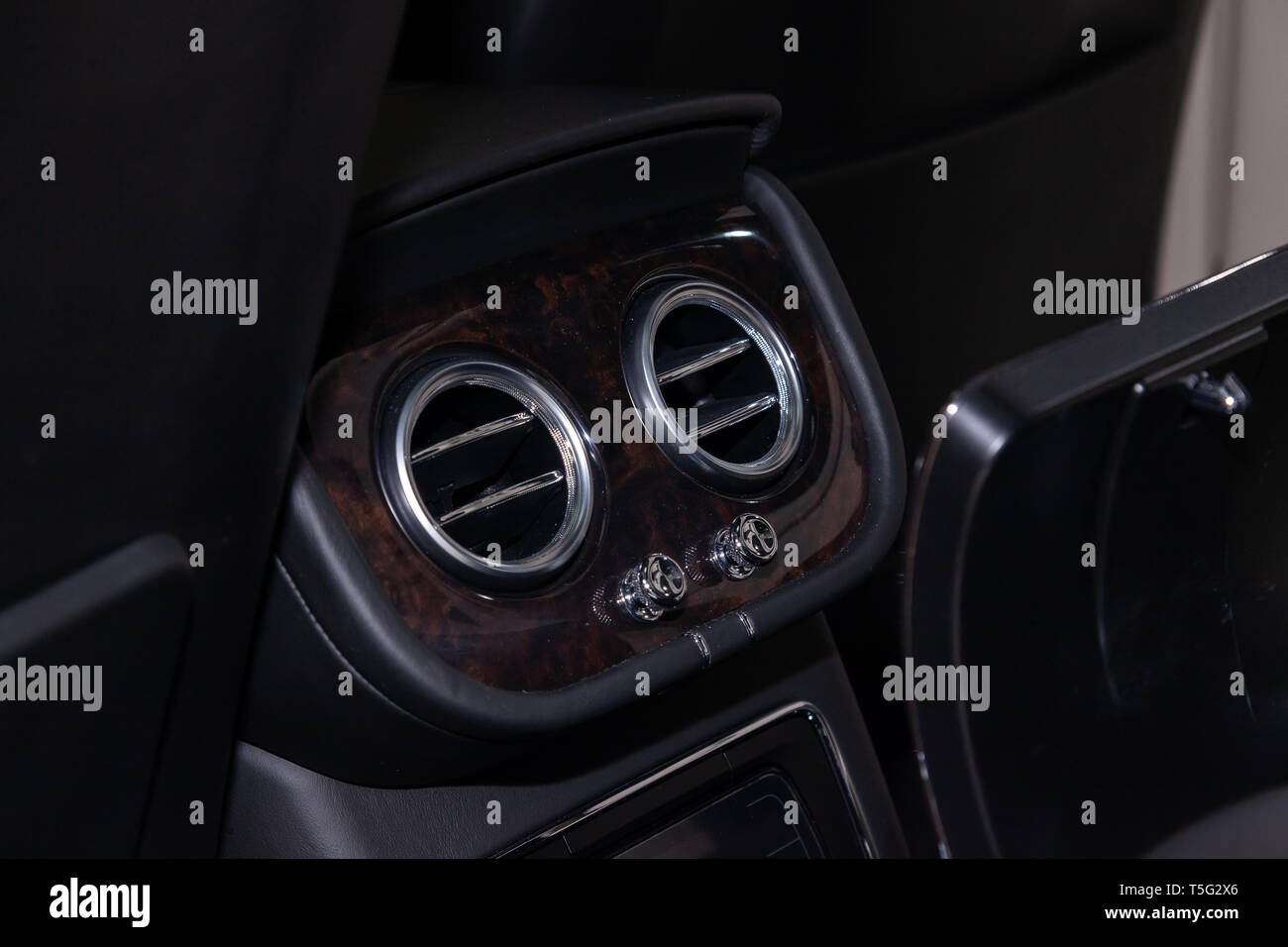 A close-up view of a part of the interior of a modern luxury car with a view of the two rear central ventilation chrome round deflectors of the stove  - Stock Image