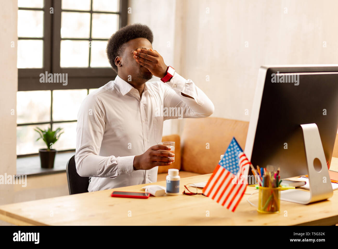 Nice good looking man taking his medicine - Stock Image