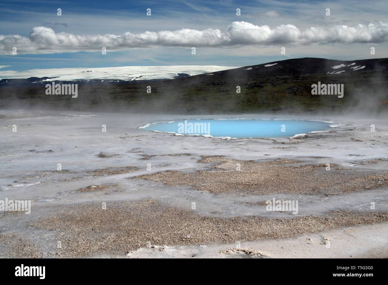 Seltun / Krysuvik (Krýsuvík): Steaming geothermal valley with natural blue pool and snowcapped mountain Stock Photo