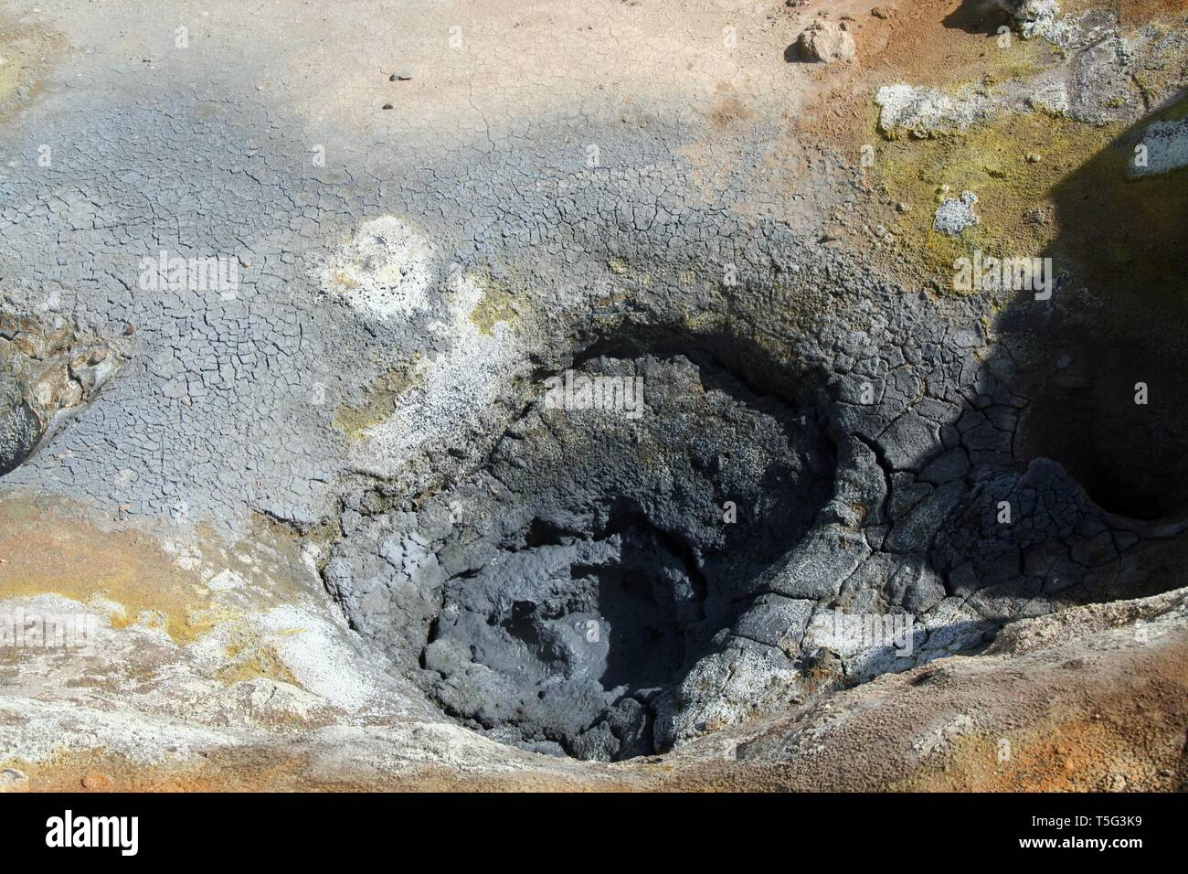 Seltun / Krysuvik (Krýsuvík): Mud pot with cracked fissured ground and deposits of yellow sulfuric acid Stock Photo