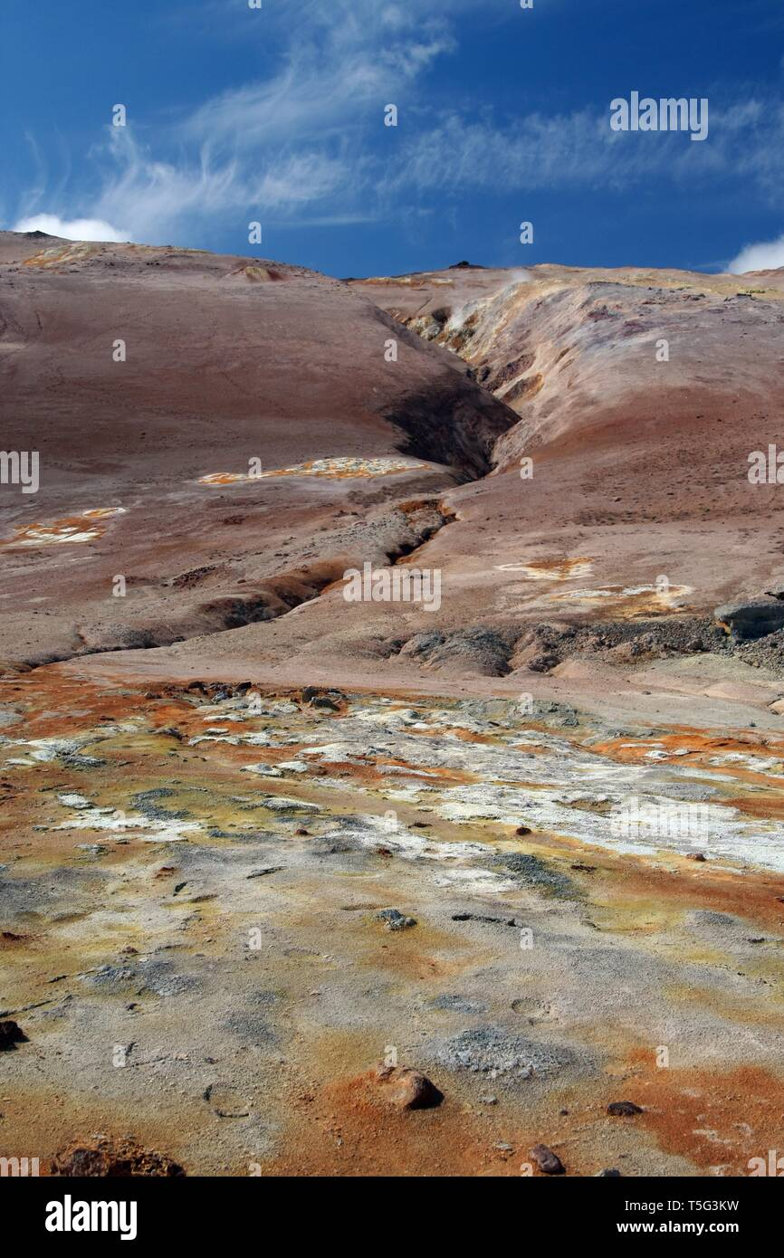 Seltun / Krysuvik (Krýsuvík): View over yellow, orange and white geothermal field on fissure of red hill contrasting with blue sky Stock Photo