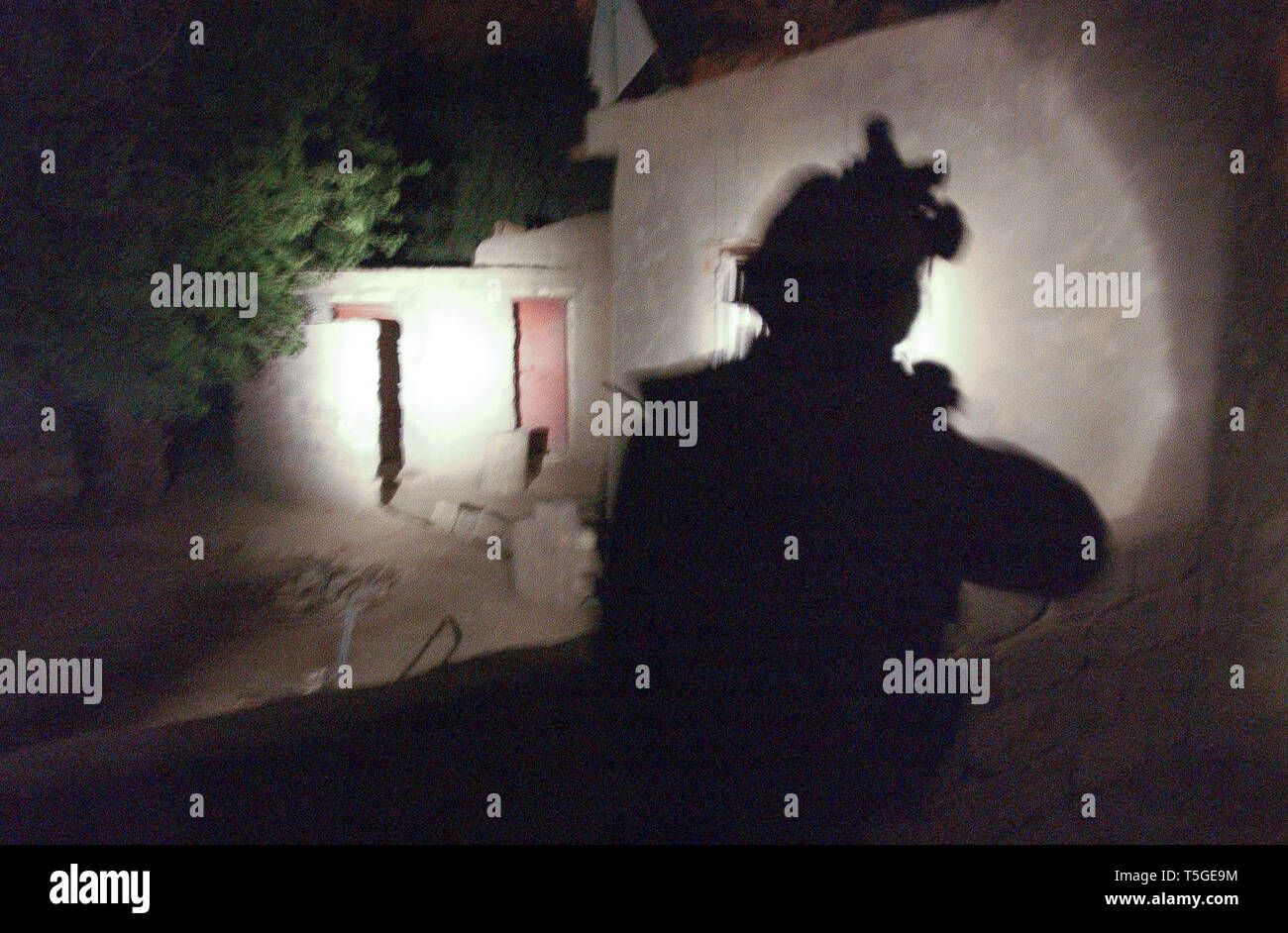 Baghdad, Baghdad, Iraq. 16th Apr, 2004. A soldier from Delta Company, 1st Battalion, 8th Cavalry Regiment shines a spot light into the home of a resident following an Improvised Explosive Device south of Baghdad, April 16, 2004. Credit: Bill Putnam/ZUMA Wire/Alamy Live News Stock Photo