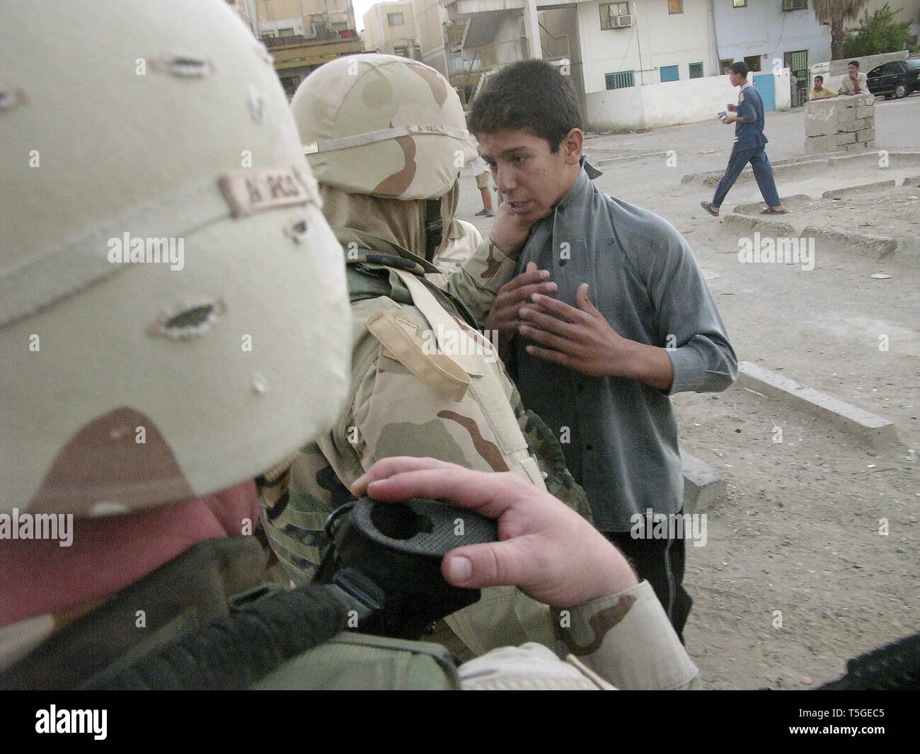 Baghdad, Baghdad, Iraq. 16th Sep, 2004. A linguist grabs an Iraqi boy by the throat during a patrol by Charlie Company, 1st Battalion, 8th Cavalry Regiment in Baghdad Sept. 16, 2004. Credit: Bill Putnam/ZUMA Wire/Alamy Live News Stock Photo