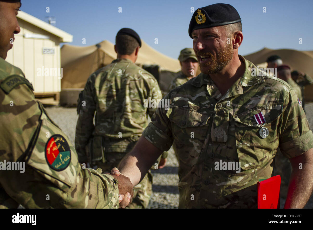 Camp Leatherneck, Helmand, Afghanistan. 25th Feb, 2012. British Royal Navy Warrant Offier Stephen Morgan is congratulated by a British servicemember after recieving the British Meritorious Service Medal (MSM) at Camp Leatherneck, Helmand province, Afghanistan, Feb. 26, 2012. Morgan recieved the British Meritorious Service Medal as a retirement medal after 32 years of service. In Afghanistan, he was a contract officer for NATO Training Mission Afghanistan's Regional Support Command Southwest. Morgan enlisted in the Royal Navy at age 16 and served in the Falklands War aboard the destroy - Stock Image
