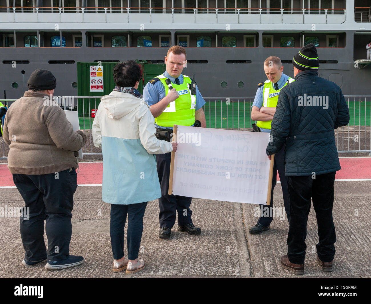Cobh, Cork, Ireland. 25th April, 2019. Members of An Garda Síochána requesting protesters to vacate the deep water quay,  at the arrival of the cruise liner L'Austral. The protesters refused to leave as they view the deep water quay as a public right of way. The protest is about  the decision by the Port of Cork Company to close the quayside public walk during the arrival of cruise liners in Cobh, Co. Cork, Ireland. Credit: David Creedon/Alamy Live News - Stock Image