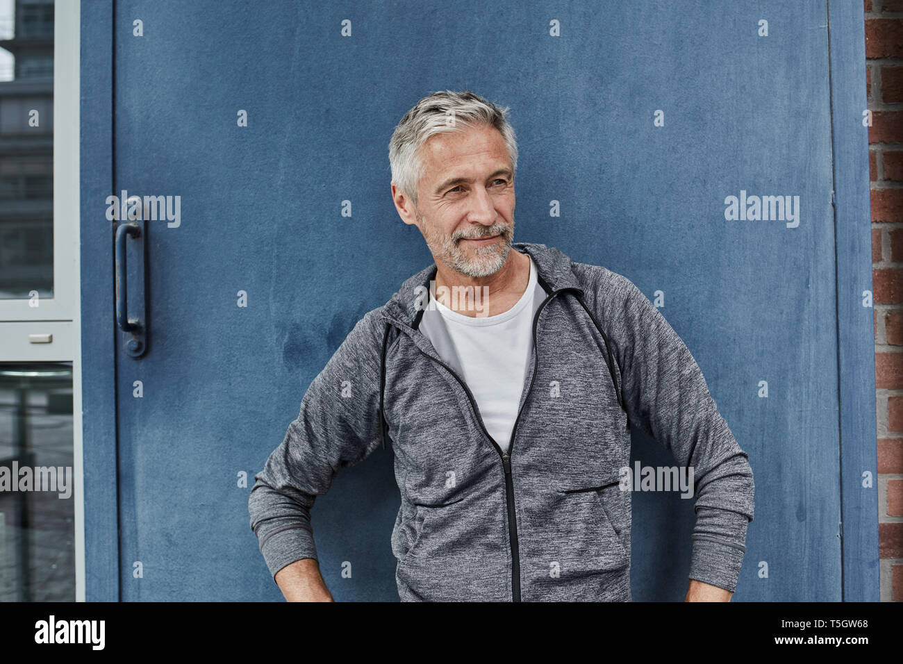 Portrait of mature man wearing tracksuit top in front of gym - Stock Image