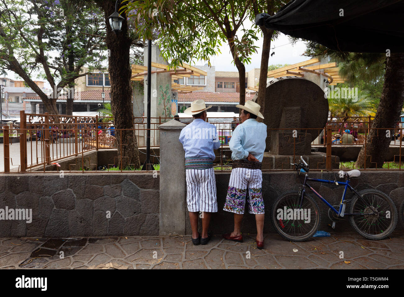 Local guatemalan men in traditional clothes talking in the street, Santiago Atitlan, Guatemala Latin America - Stock Image