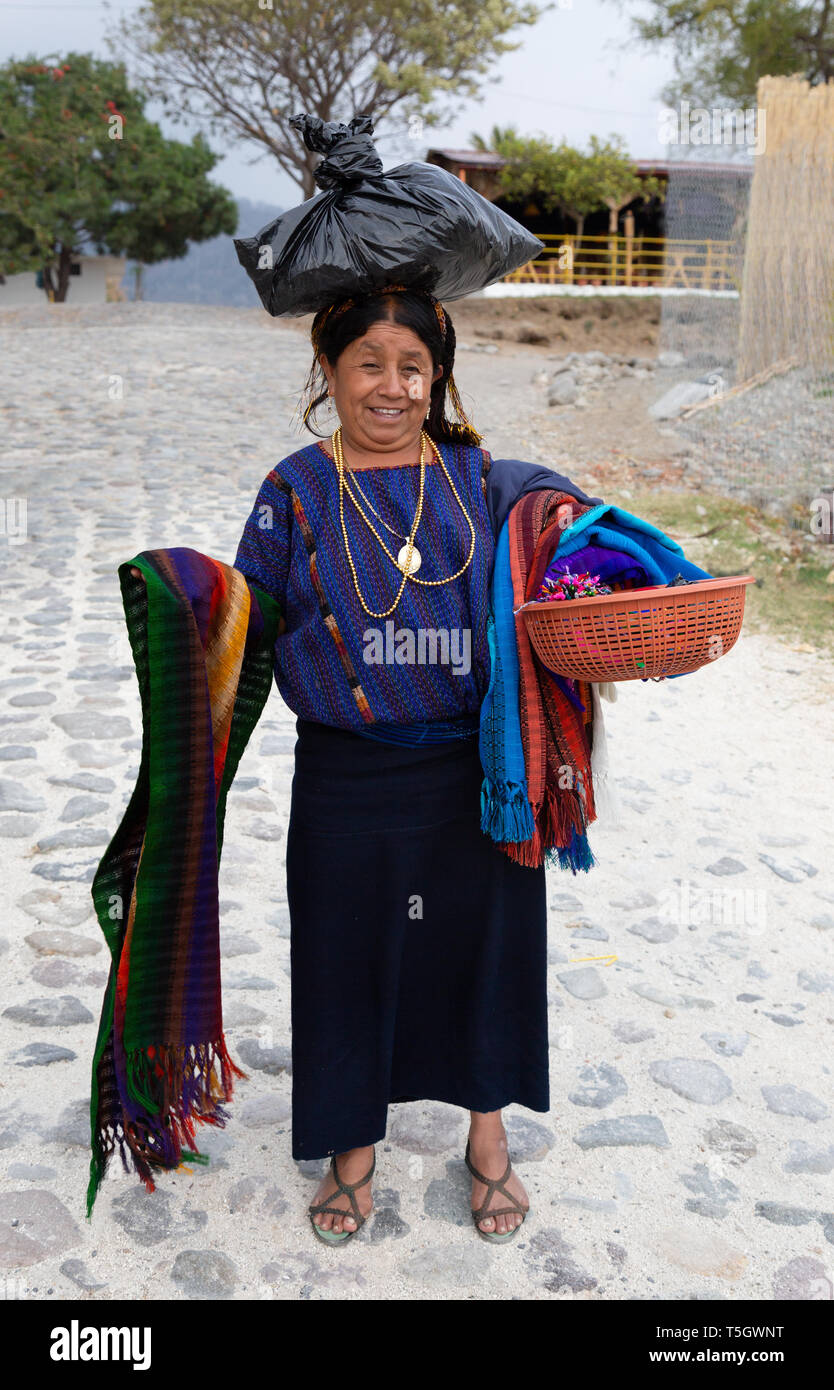 A middle aged guatemalan woman sellling scarves on the street, Santiago Atitlan town, Guatemala Central America - Stock Image