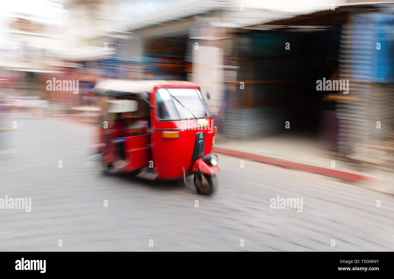 A speeding tuk tuk taxi or auto rickshaw with motion blur; Guatemala, Central America - Stock Image
