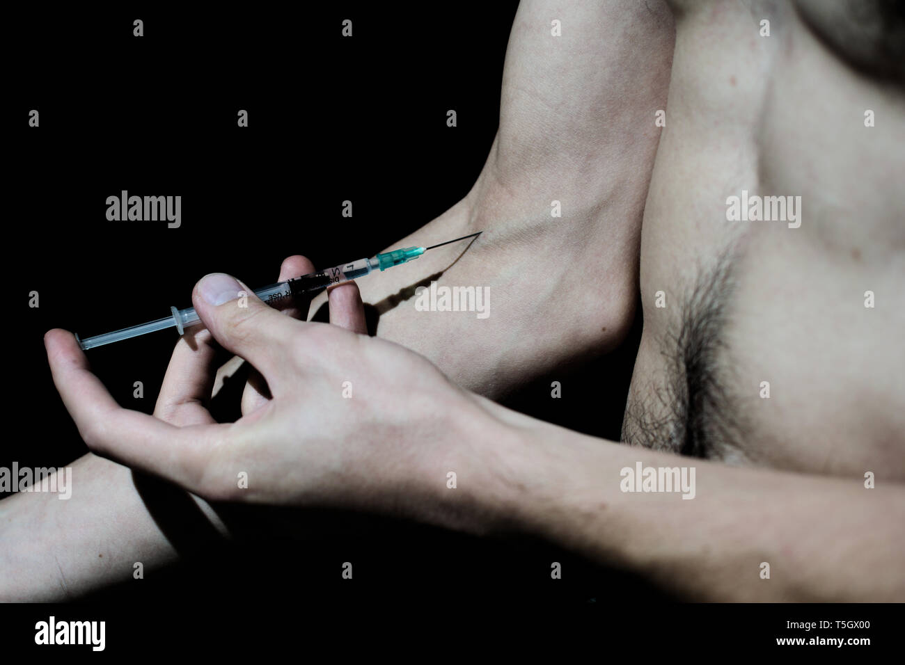 Dark studio shot of a bare chested man injecting heroin - Stock Image
