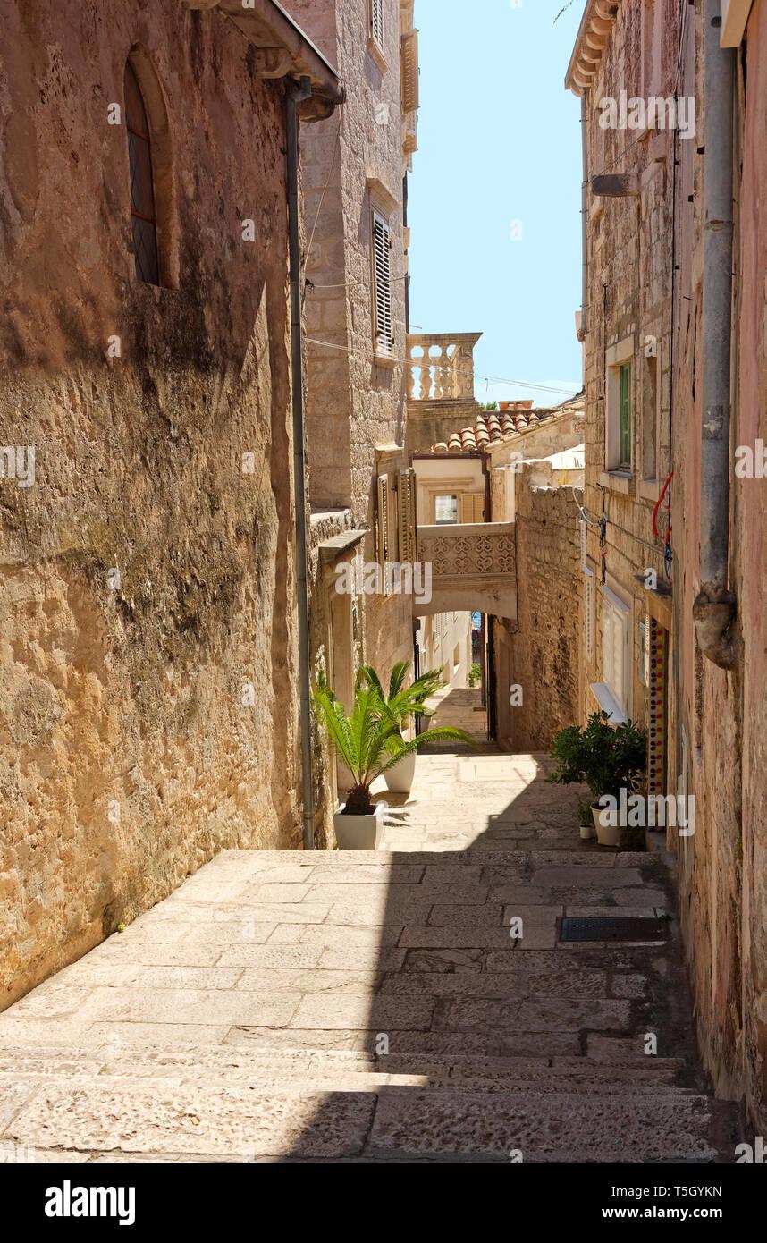narrow pedestrian street; descending, steps, 15th century; old stone buildings, Dalmatia; Korcula Town; Croatia; Europe; summer, vertical - Stock Image