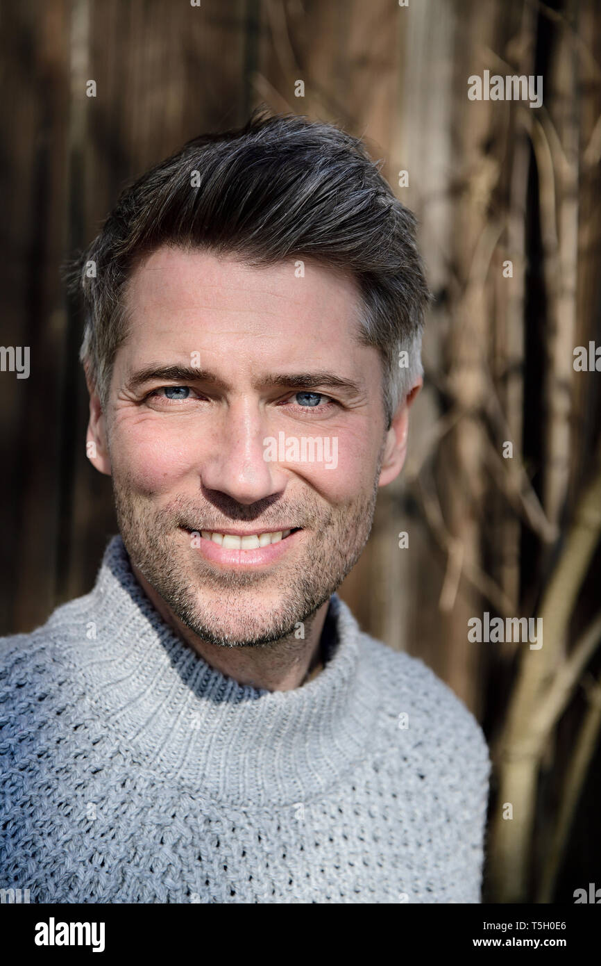 Portrait of mature man with greying hair and grey pullover - Stock Image