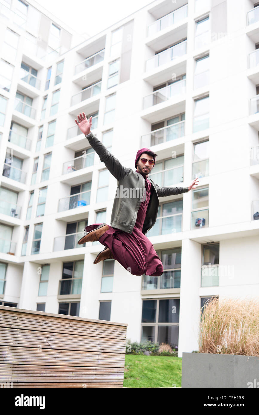 Full length of stylish man in purple hat and Indian costume jumping over modern building with widened arms - Stock Image
