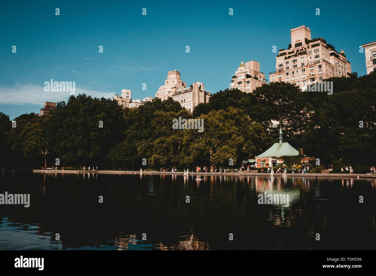 A reflecting lake in a park with tall buildings, trees and a beautiful sky Stock Photo