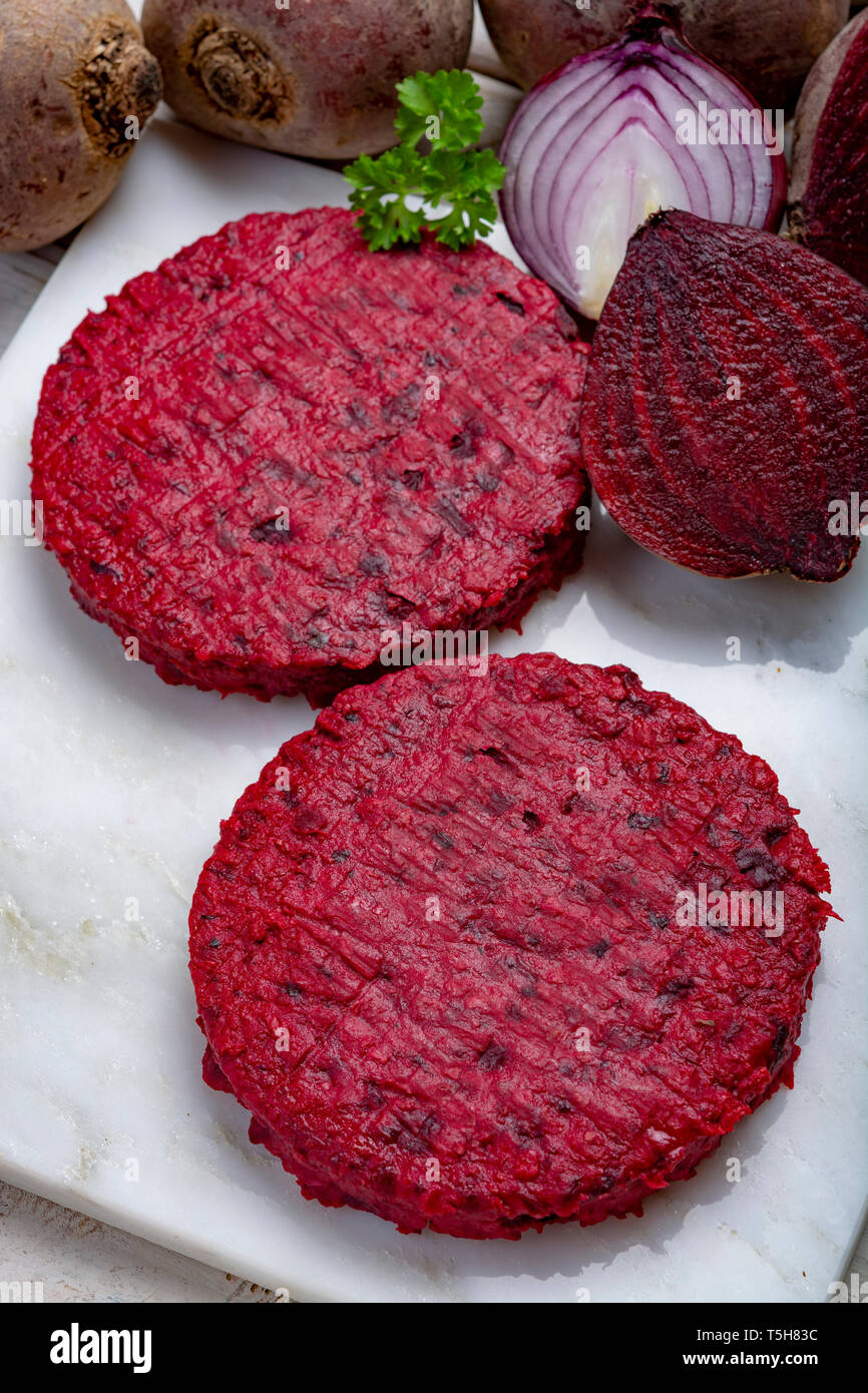 Healthy vegetarian food, raw round burgers made from red beetroot close up, good for vegans Stock Photo