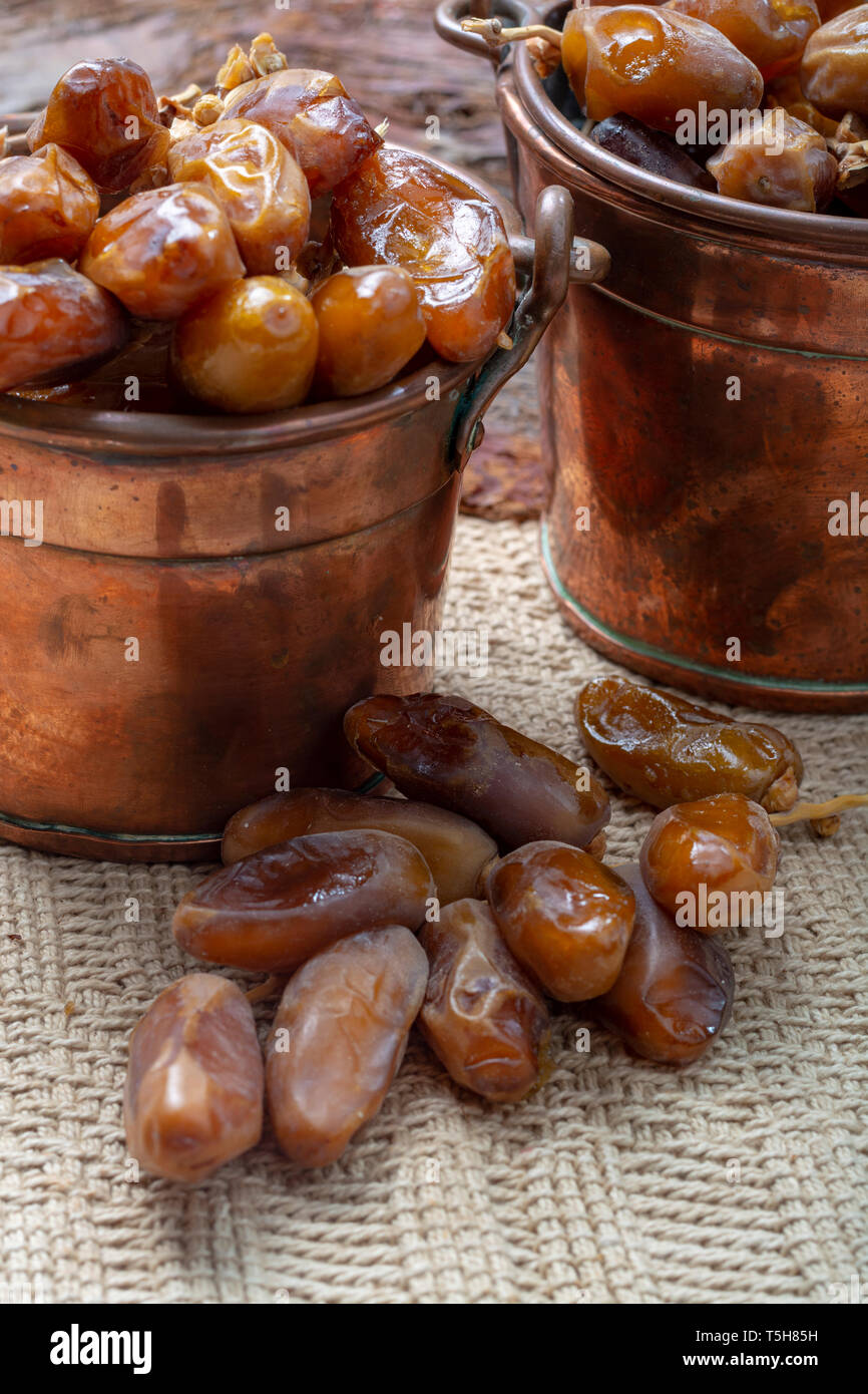 Authentic Tunisian Deglet Nour dried dates with soft honey-like taste in copper buckets Stock Photo