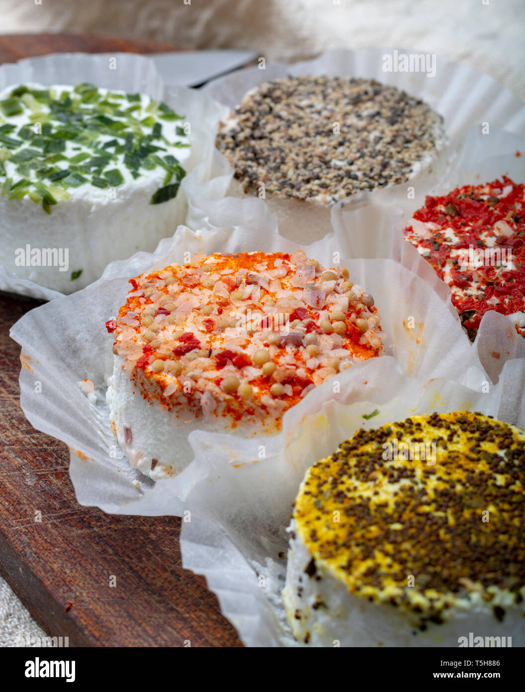 Colorful assortment of French fresh white soft goat cheeses with different tastes topping made with herbs, paprika, indian curry, bruscetta, chives an Stock Photo