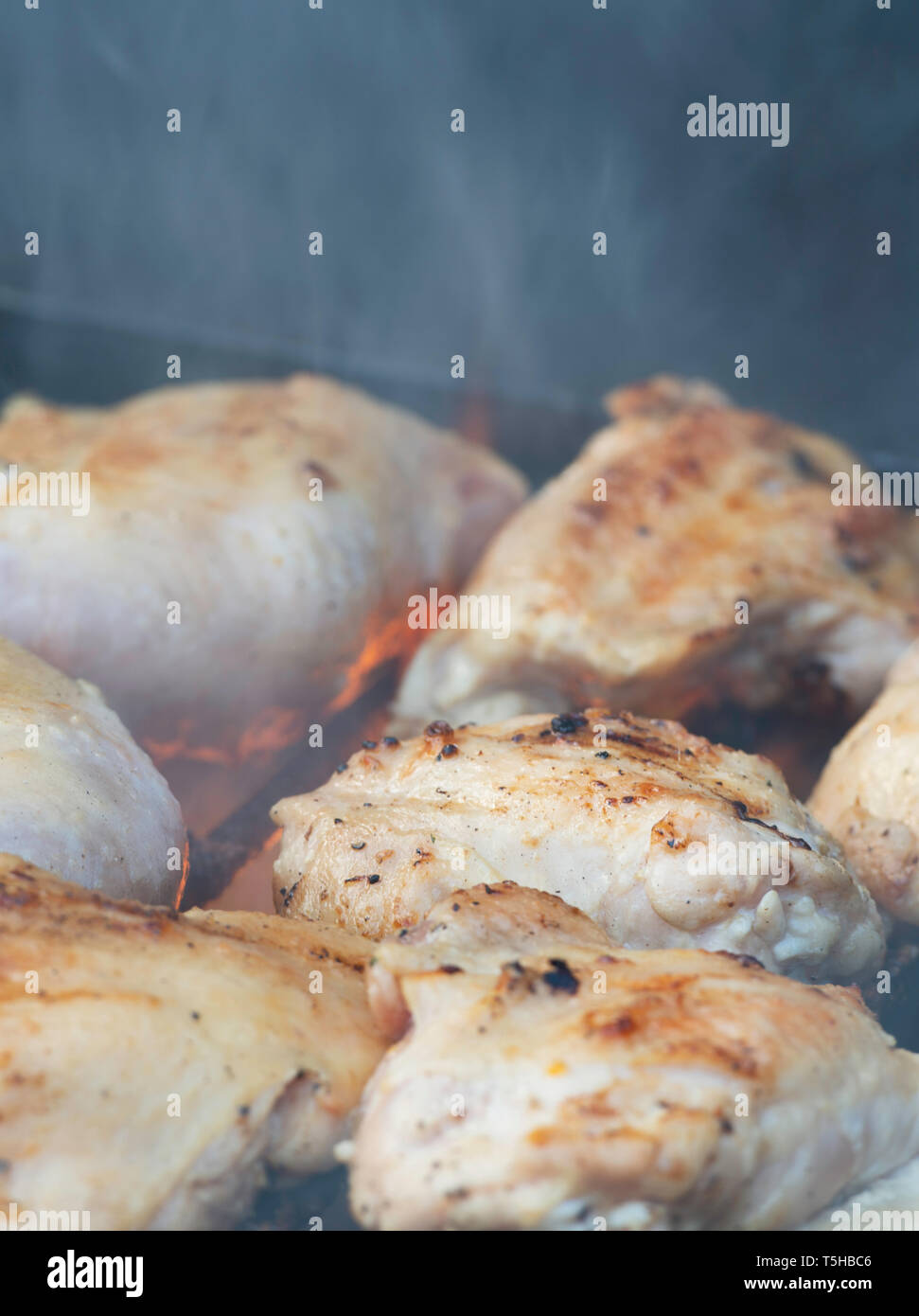 grilling chicken tights on bbq  for a party at a backyard, outdoor - Stock Image
