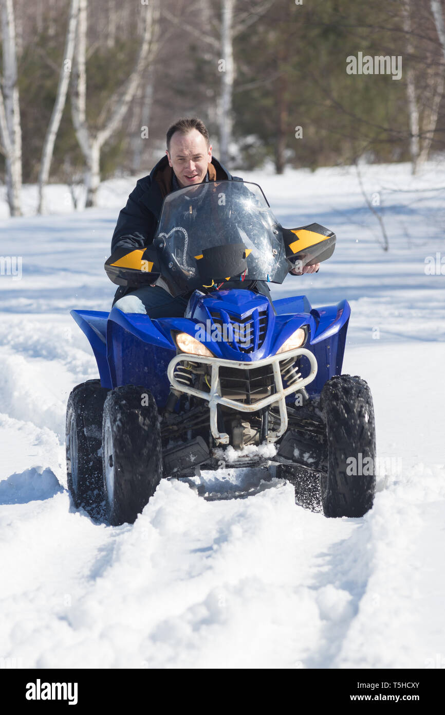 A man in winter clothes riding snowmobile in the winter forest - Stock Image