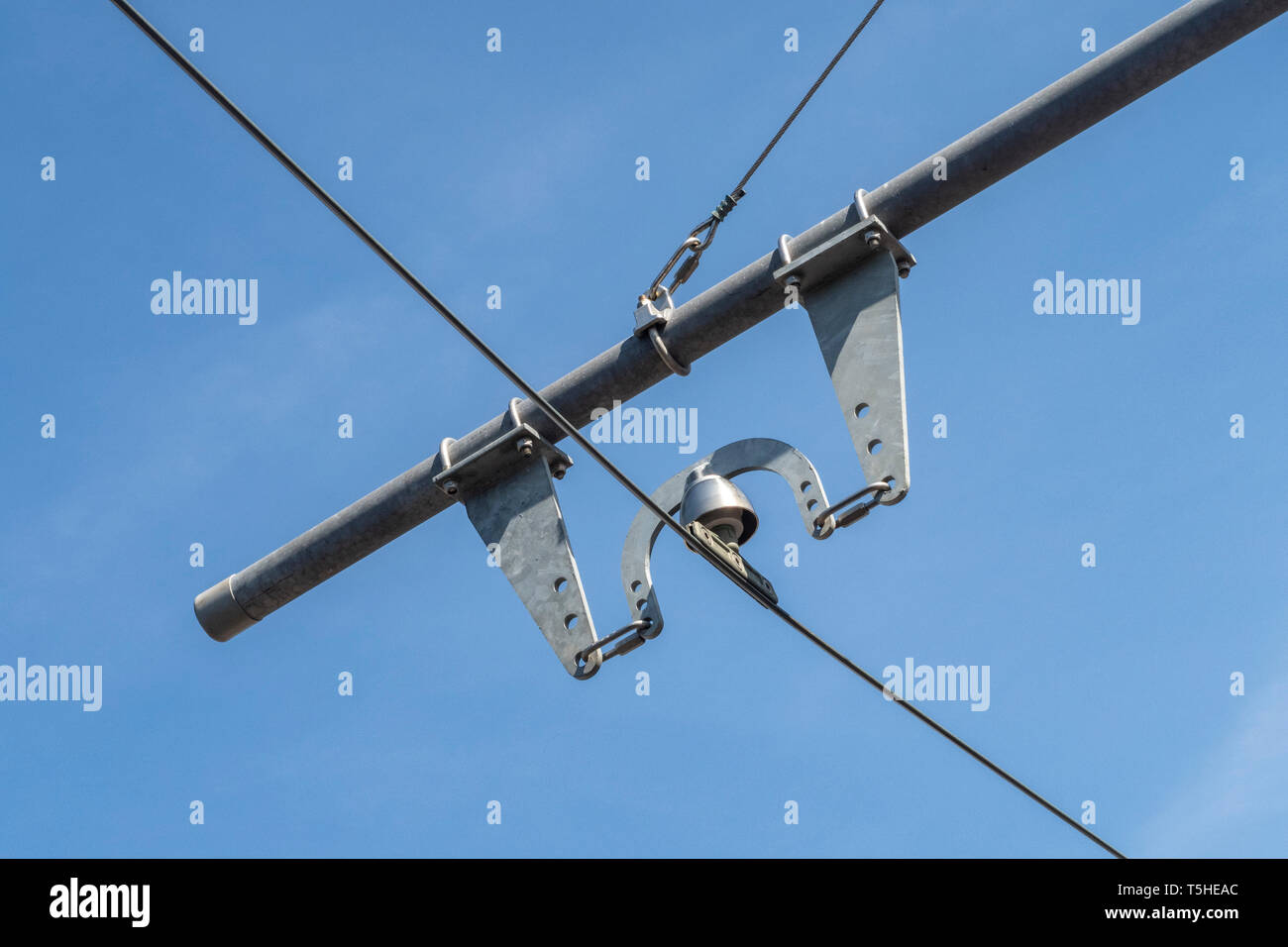 Electricity poles and lines at Seaton tramway, Devon, Uk, with a blue sky behind. Stock Photo