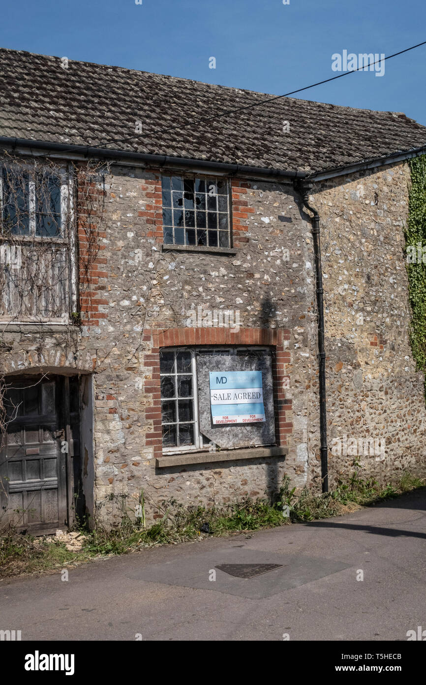 Run down derelict building in Colyton, Devon, UK, with sale agreed sign.Overgrown, with broken windows. Stock Photo
