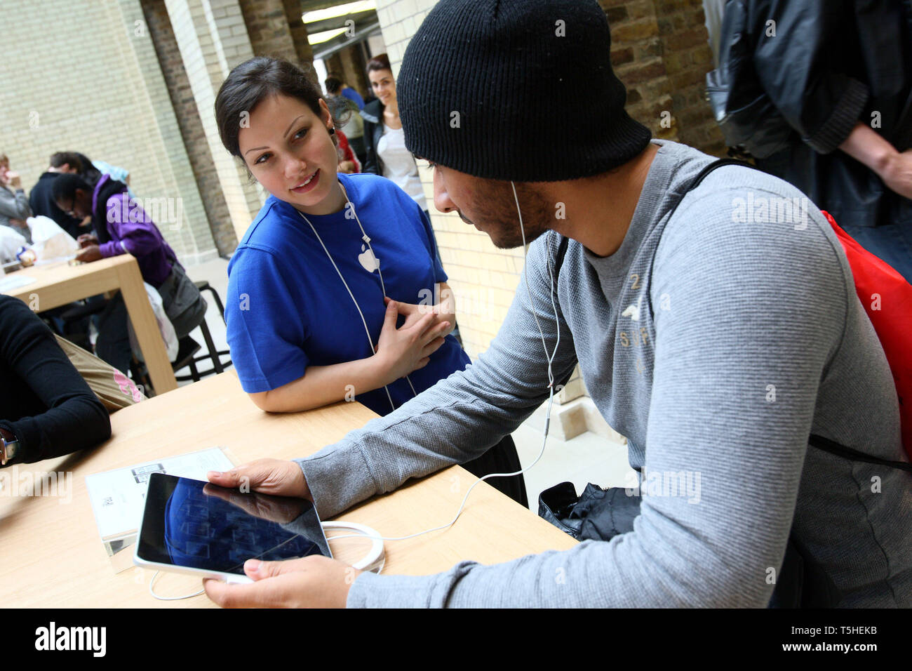 Staff giving advice on using the iPad at Apples Covent Garden store in London. 7 August 2010. - Stock Image
