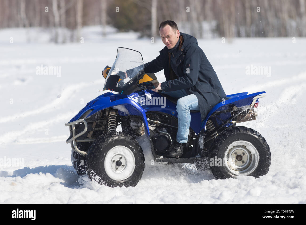 A winter forest in daylight. A man riding a big blue snowmobile. Side view Stock Photo