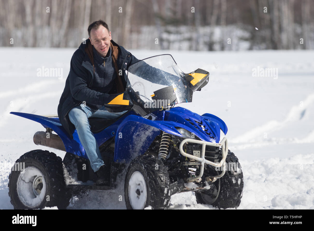 A winter forest. Cold weather. A man riding a big snowmobile Stock Photo