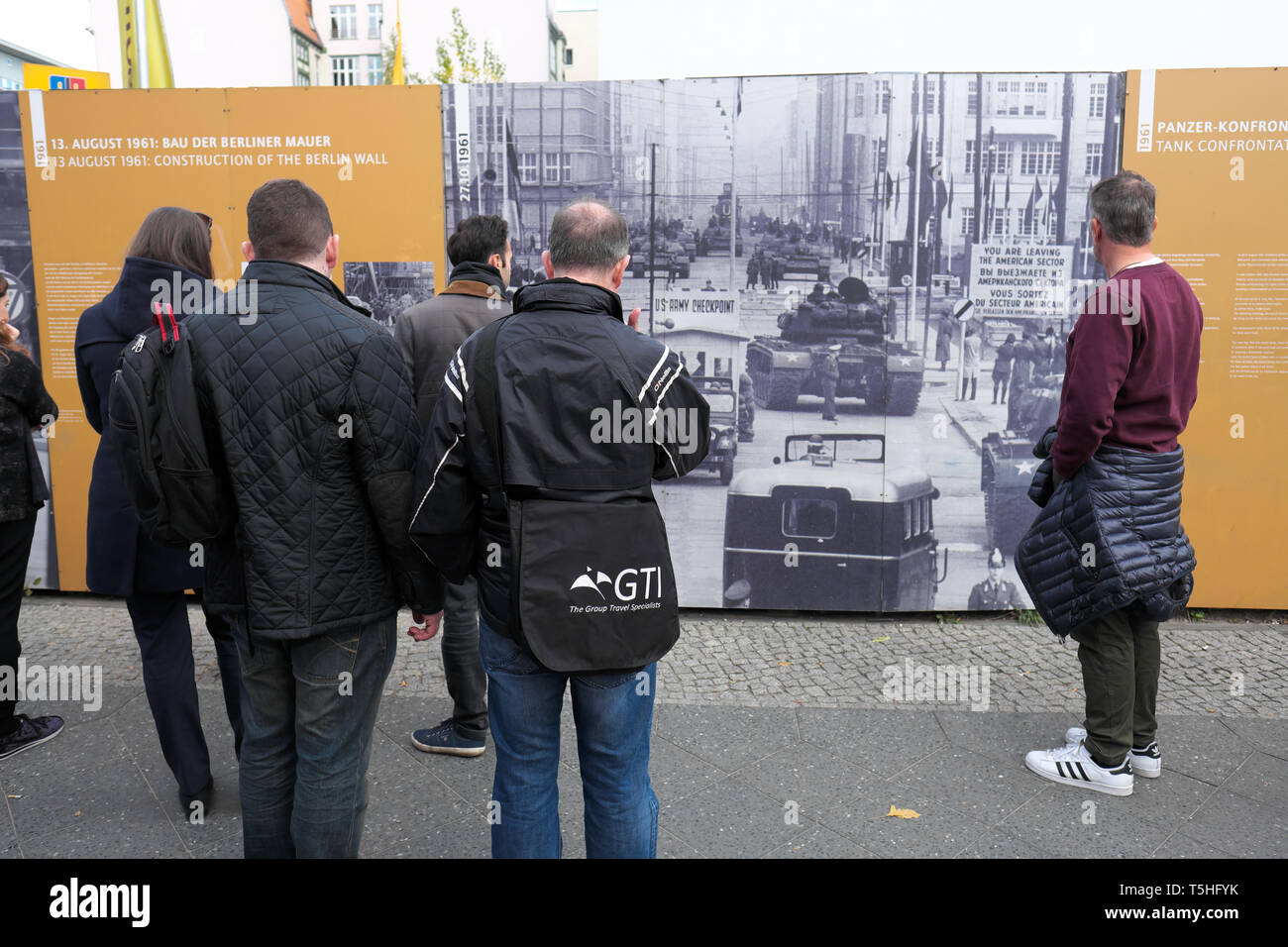 Berlin, Germany - tourists and visitors look at a Cold War era photo of the Checkpoint Charlie border crossing at the same location today - Stock Image