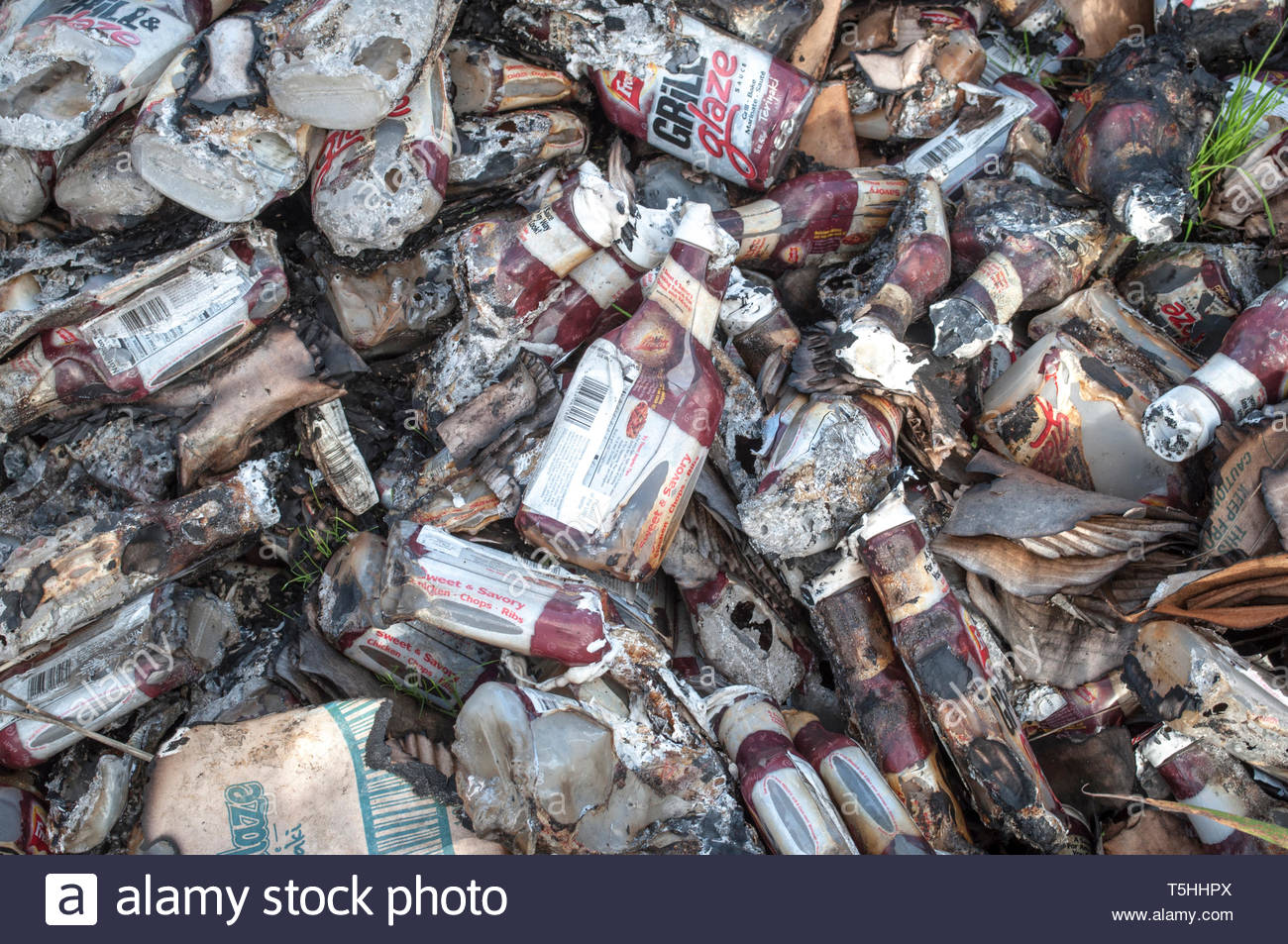 Partially incinerated bottles of barbecue sauce abandoned on waste ground, Willenhall; West Midlands. - Stock Image