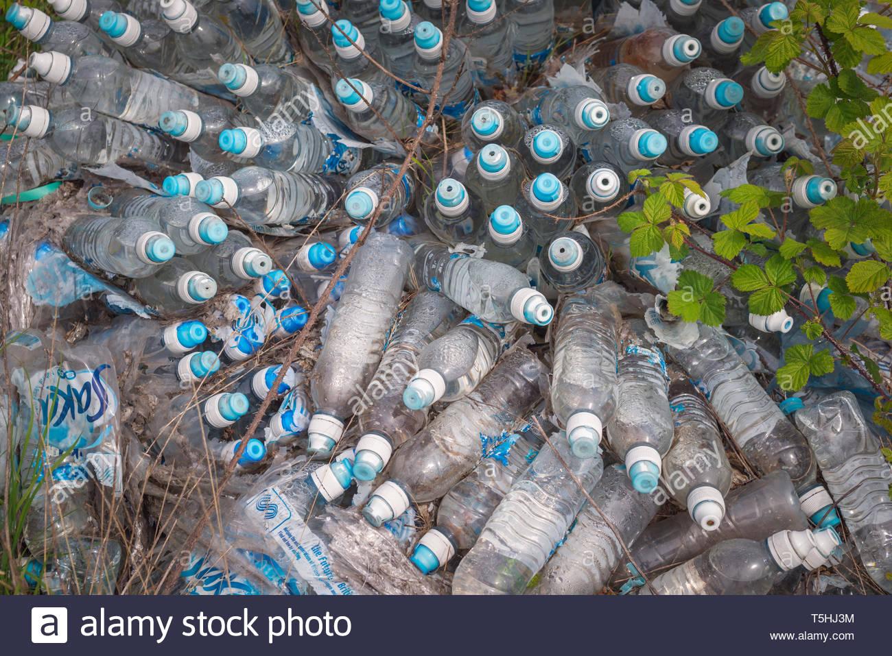 Unused bottles of mineral water dumped on wasteland, Birmingham, UK. - Stock Image