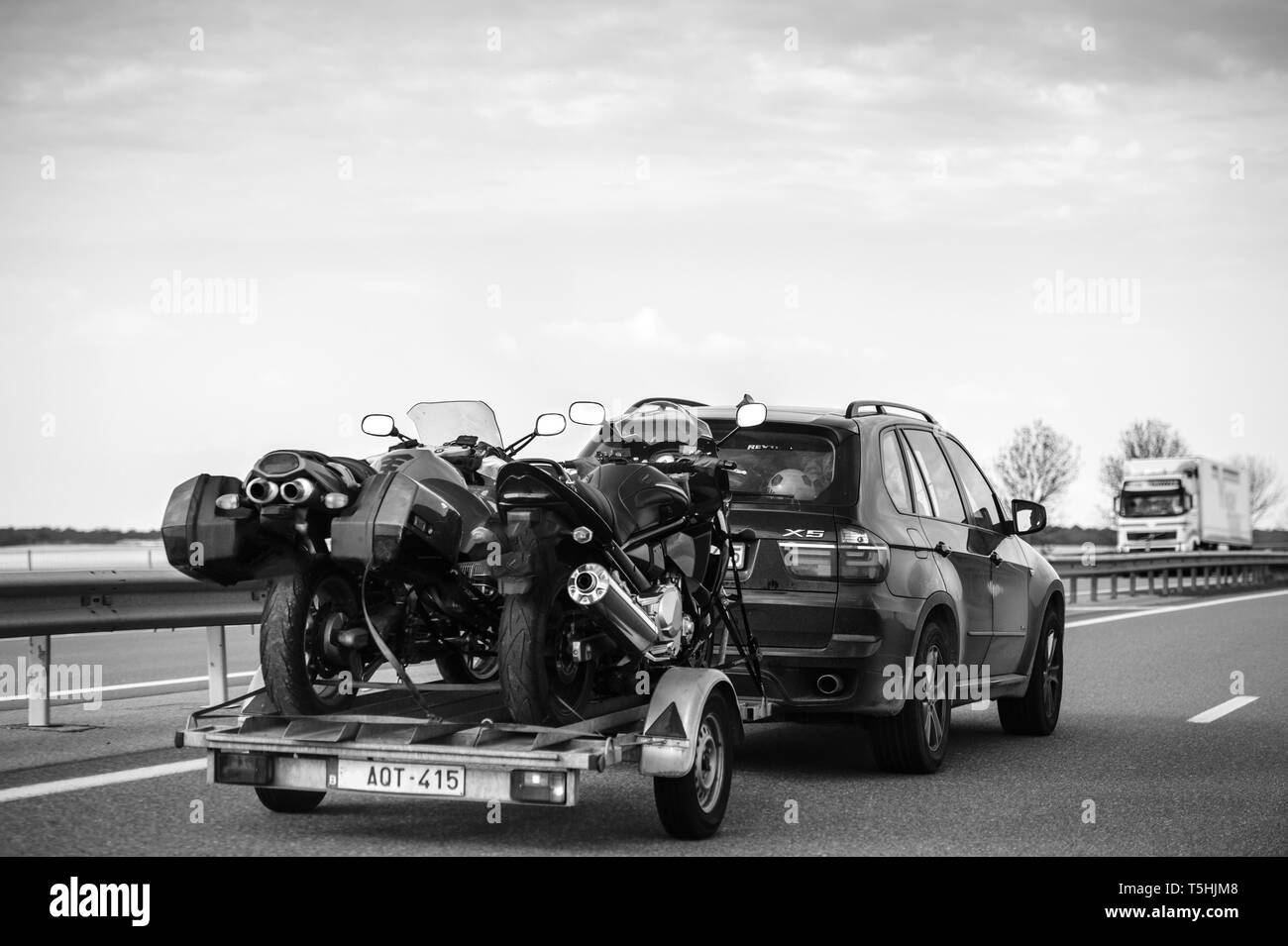 Nice, France - May 7, 2016: Rear view of BMW suv X5 driving fast on French highway with trailer holding two fast motorcycles for motocross - black and white  - Stock Image