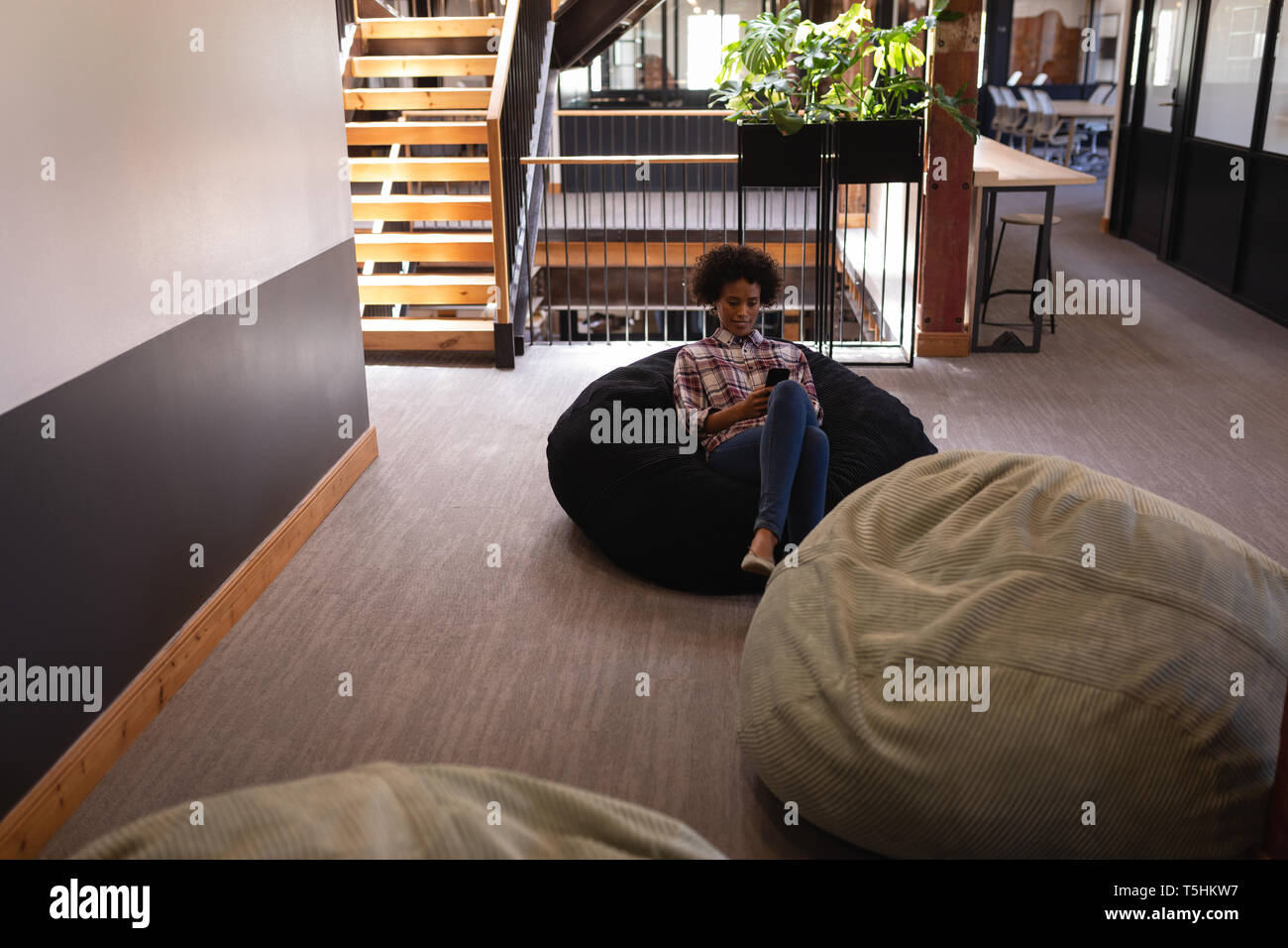 Businesswoman using mobile phone while relaxing at bean bag - Stock Image