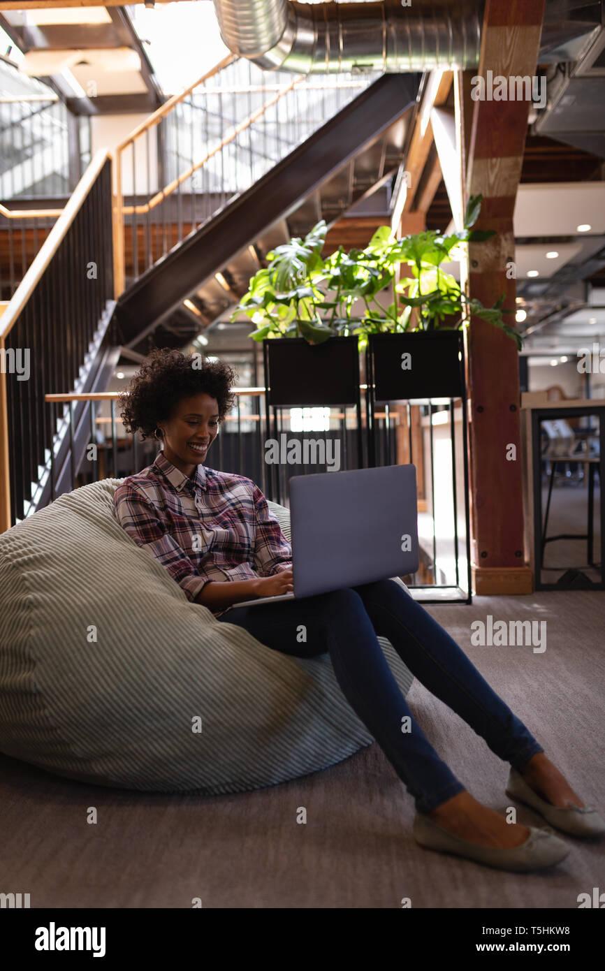 Businesswoman using laptop while relaxing at bean bag - Stock Image
