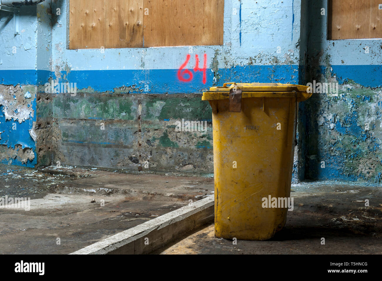 Yellow garbage can alone in factory - Stock Image