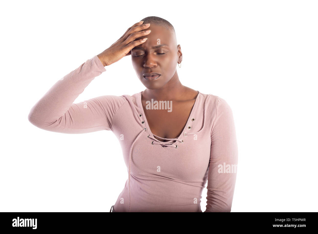Black african american female model with bald hairstyle wearing a pink shirt on a white background looking sick with headache or migraine - Stock Image