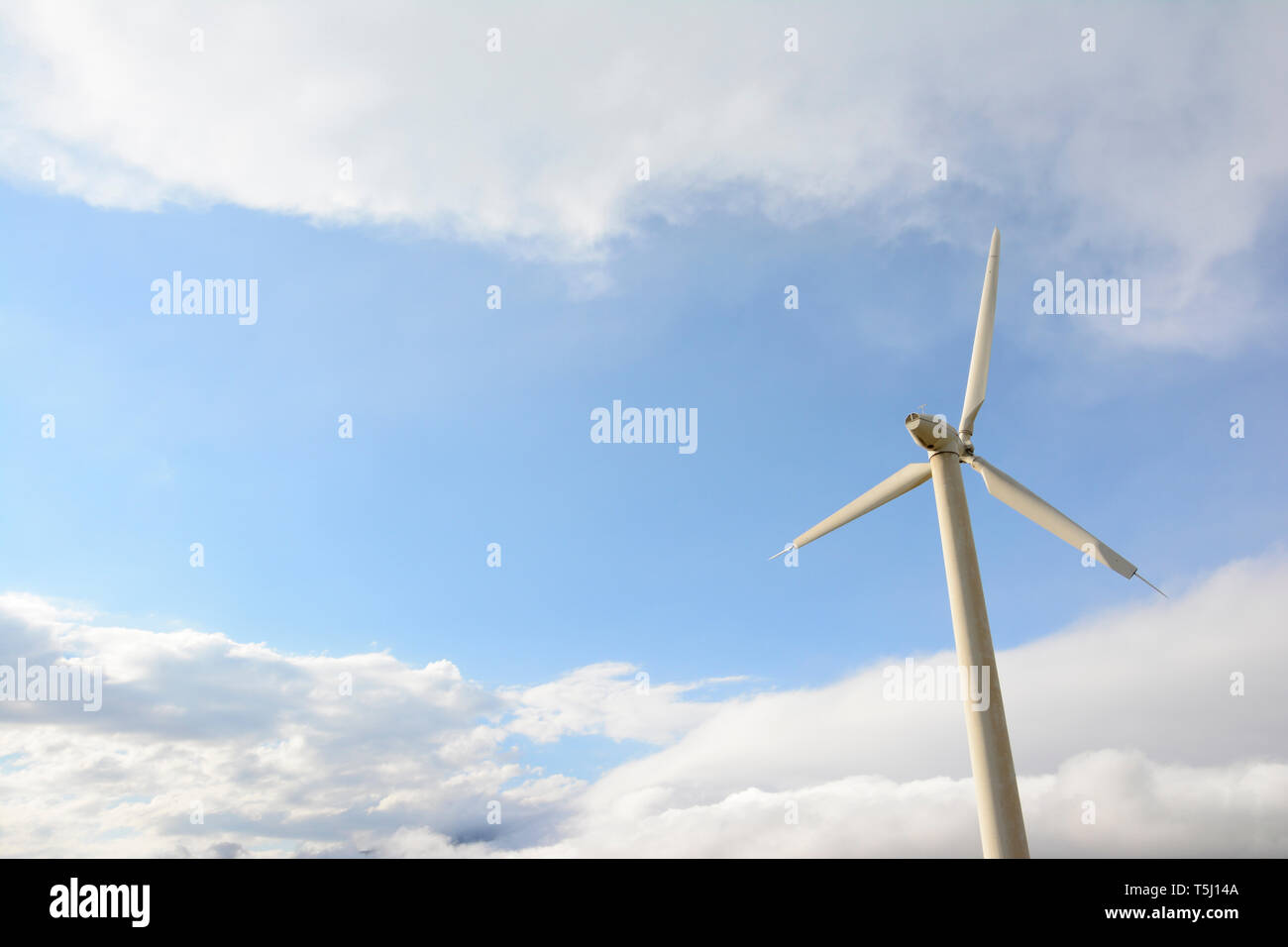 Single windmill in front of cloudy sky, environmentally friendly electricity production - Stock Image