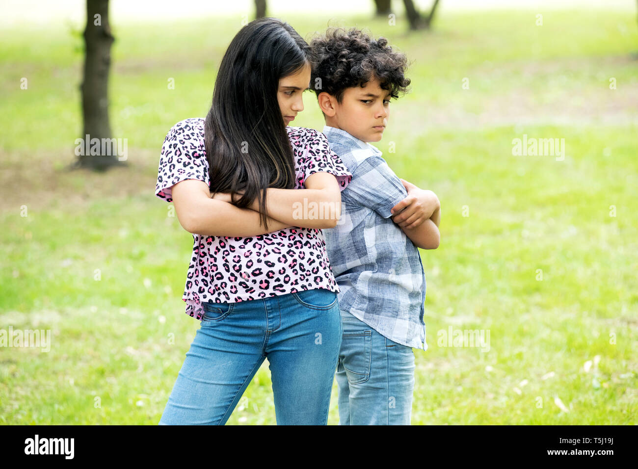 Brother and sister after an argument standing back to back with folded arms scowling outdoors in a garden Stock Photo