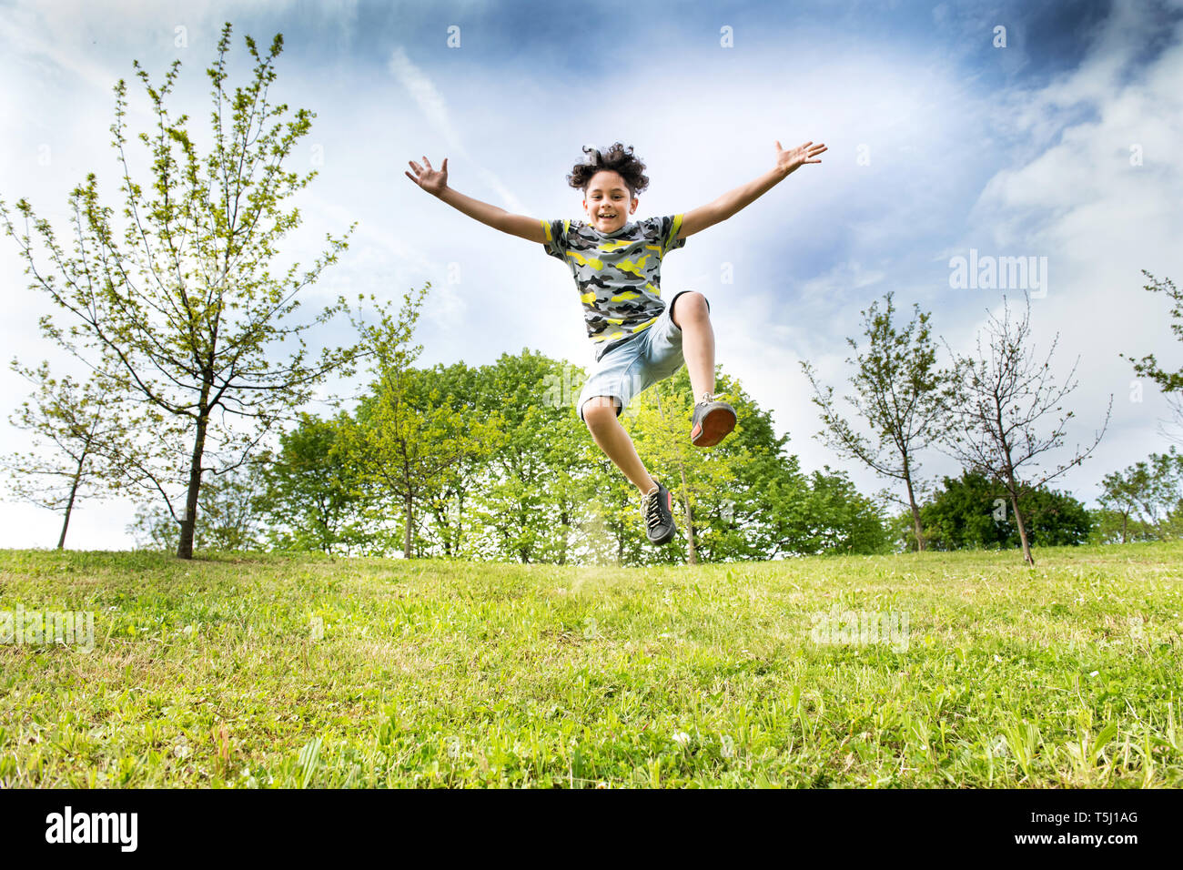 Happy energetic young boy jumping high in the air as he runs across the grass in a garden or park with outstretched arms in a low angle view - Stock Image