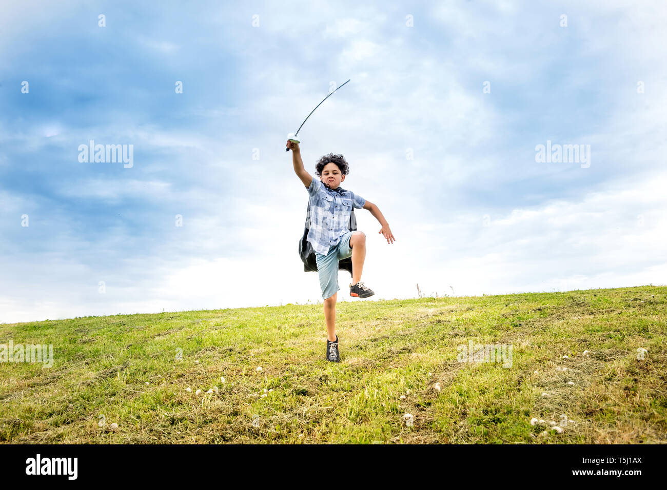 Young boy having fun playing soldiers brandishing a toy sword above his head as he runs across a green grassy hill - Stock Image