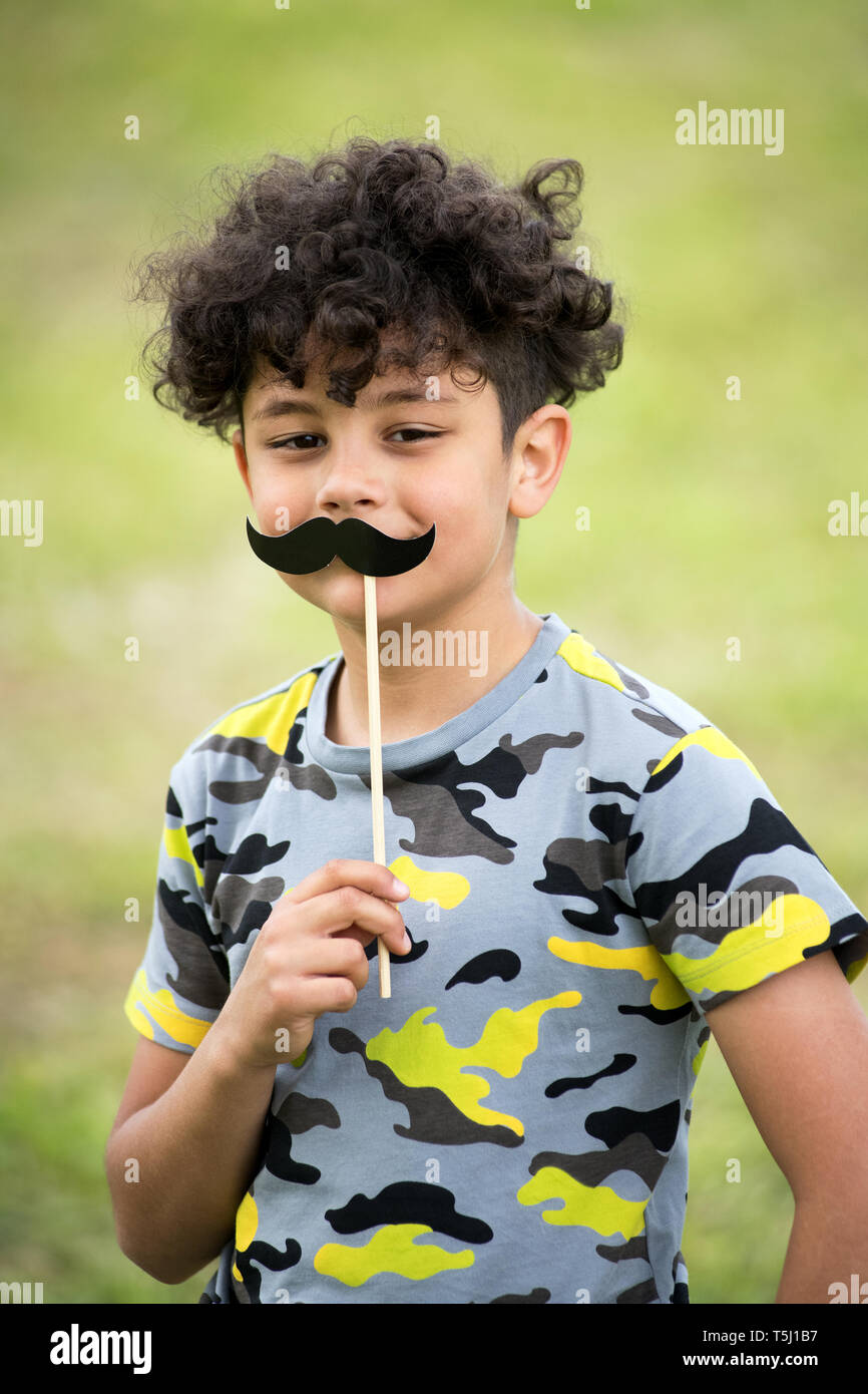 Playful young boy holding up a mustache party accessory with smiling eyes outdoors against blurred green grass Stock Photo