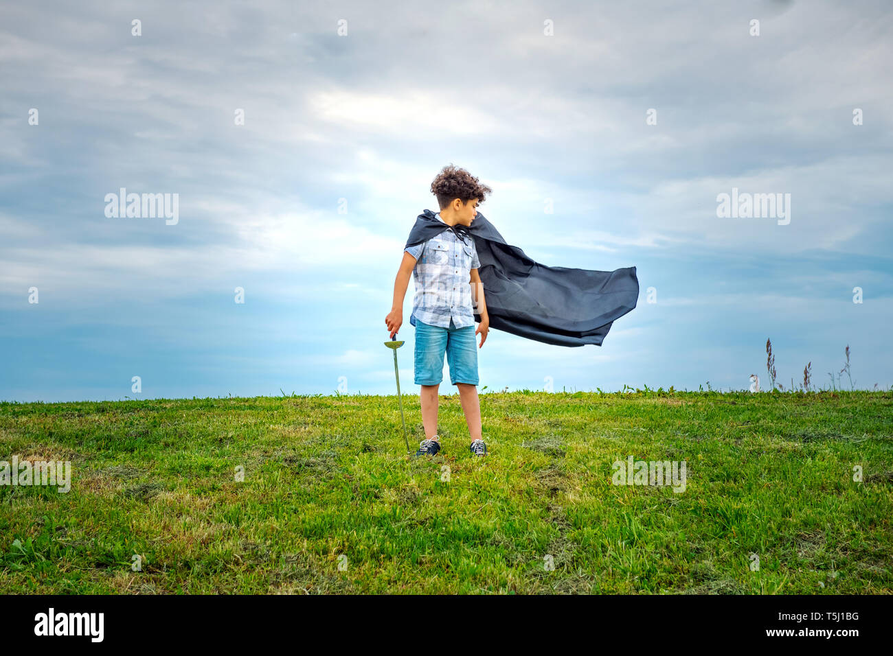 Young boy super hero with blowing cloak standing outdoors in a green field in the wind looking behind to watch it billow in the breeze - Stock Image