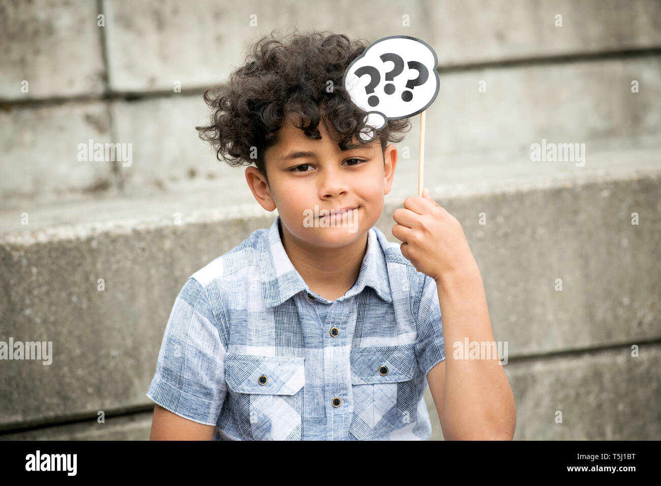 Confused young boy sitting thinking deeply with question marks on a party favor holding them to his head with a charismatic smile as he sits outdoors  - Stock Image