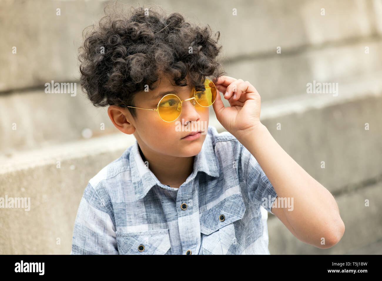 Young curly headed boy with trendy yellow round shades or sunglasses sitting outdoors looking to the side with a serious expression - Stock Image